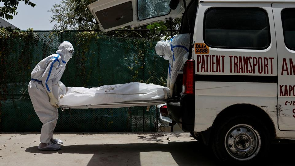 Mortuary workers load the body of a person who died from the coronavirus disease into an ambulance.While medical staff work tirelessly to save as many lives as possible, scenes of loss also play out in the same facility. Mourning relatives looked on, as the body bag was loaded into an ambulance and taken away to a cemetery. (Danish Siddiqui / REUTERS)