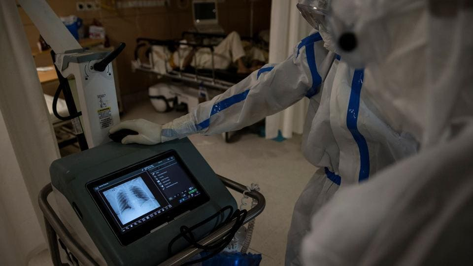 Medical workers look at the chest scan reports of a patient in the ICU. The eerie calm in the hospital is broken only by the sound of machines beeping and patients coughing --most of whom are separated only by white curtains. Staff in heavy protective gear move around softly, speaking in murmurs. (Danish Siddiqui / REUTERS)