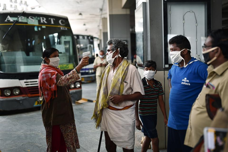 An APSRTC worker conducts thermal screening of a passenger before at Pandit Nehru Bus Station, Vijayawada, Andhra Pradesh, during the ongoing COVID-19