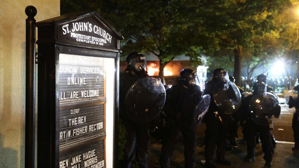 Law enforcement personnel clash with protesters rallying against the death in Minneapolis police custody of George Floyd, near St. John's Church in Washington.