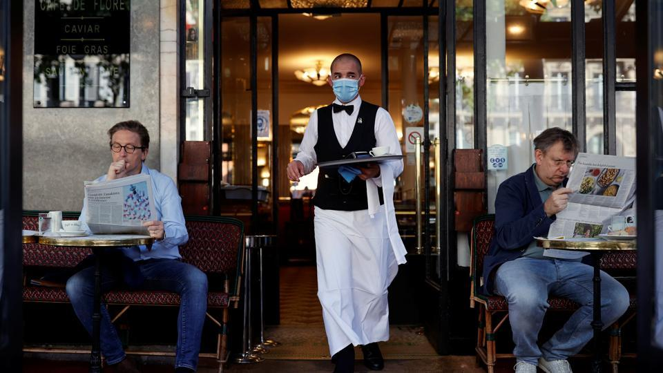 A waiter wearing a face mask serves at Cafe de Flore, as restaurants and cafes reopen following the coronavirus disease (COVID-19) outbreak, in Paris, France, June 2, 2020. REUTERS/Christian Hartmann