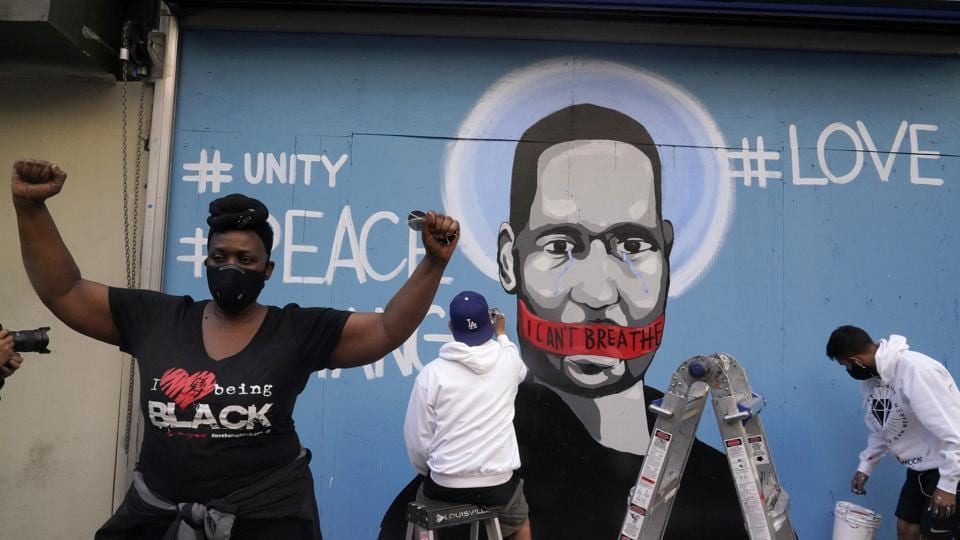 A woman gestures while a mural with an image of George Floyd is painted in the background during a rally against the death in Minneapolis police custody of George Floyd, in Los Angeles, California, US.