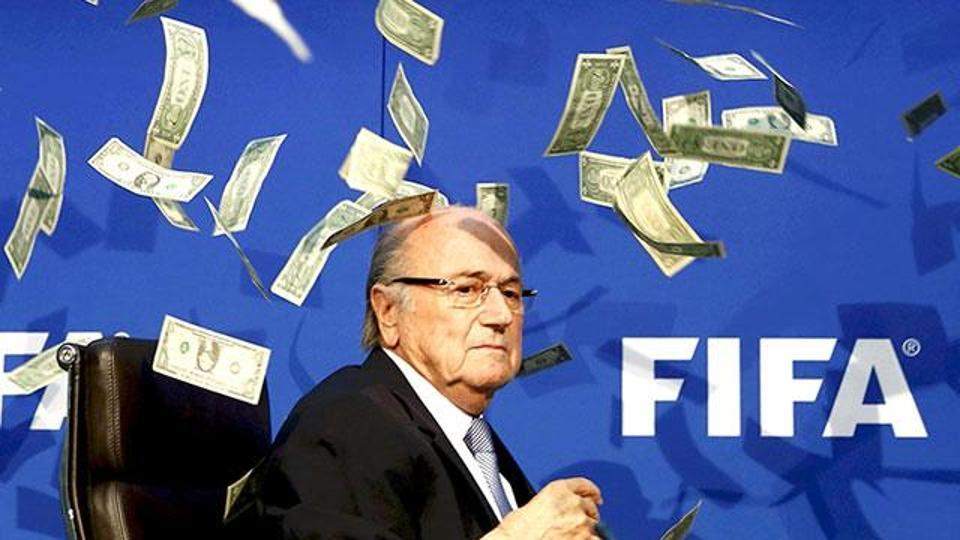 British comedian Lee Nelson (unseen) throws fake money bills at FIFA president Sepp Blatter at a news conference in Zurich on July 20, 2015.