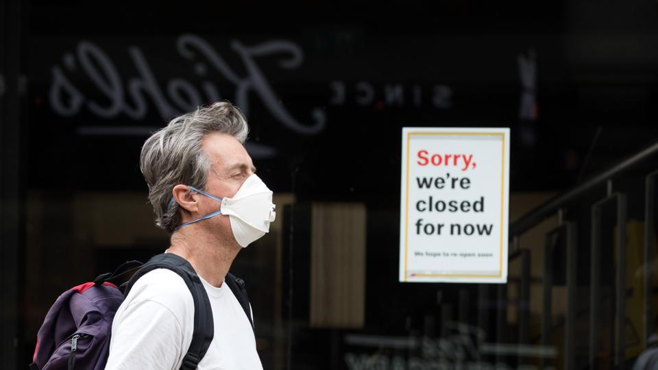 A pedestrian wearing a protective face mask passes a temporarily closed fast-food restaurant in Oxford, UK.