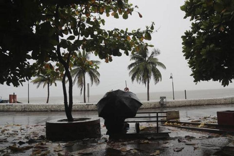 A man sit on a bench as it rains by the shores of the Arabian Sea in Mumbai.