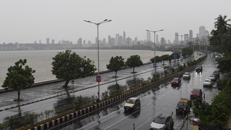 Commuters drive along Marine Drive as rain falls in Mumbai on June 3, 2020 as cyclone Nisarga barrels towards India's western coast.