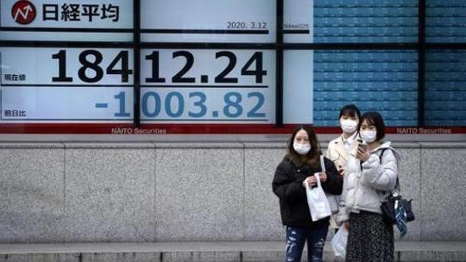Women stand in front of at an electronic stock board showing Japan's Nikkei 225 index at a securities firm in Tokyo.