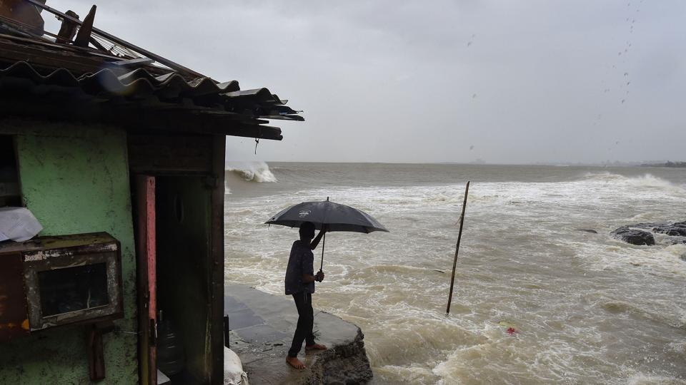 A man stands near a house built on the edge of the Arabian Sea at Bandra, ahead of Cyclone Nisarga's expected landfall, in Mumbai, on Wednesday.