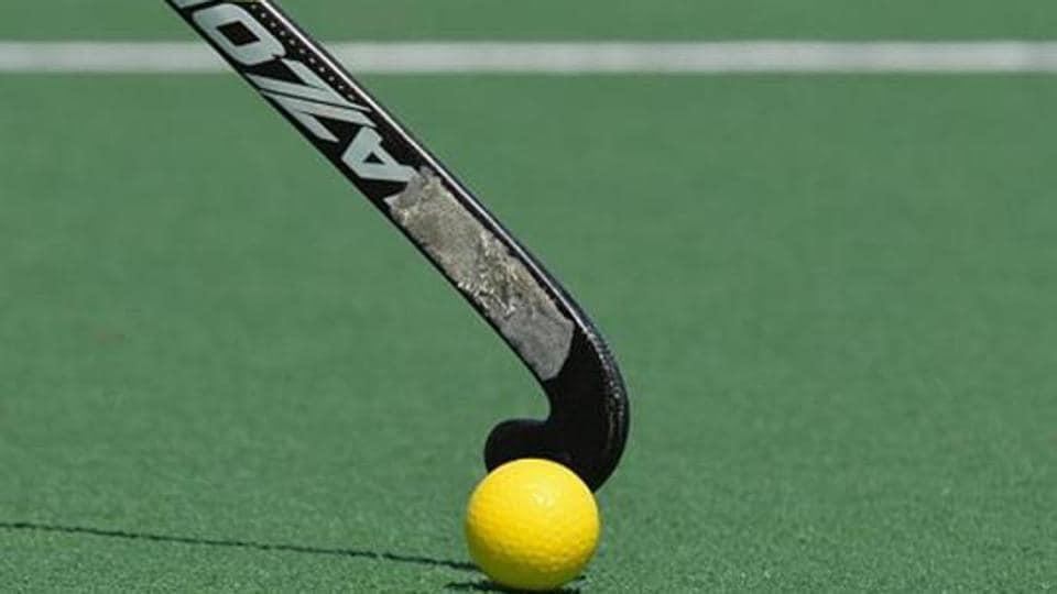 A field hockey stick hits the ball.