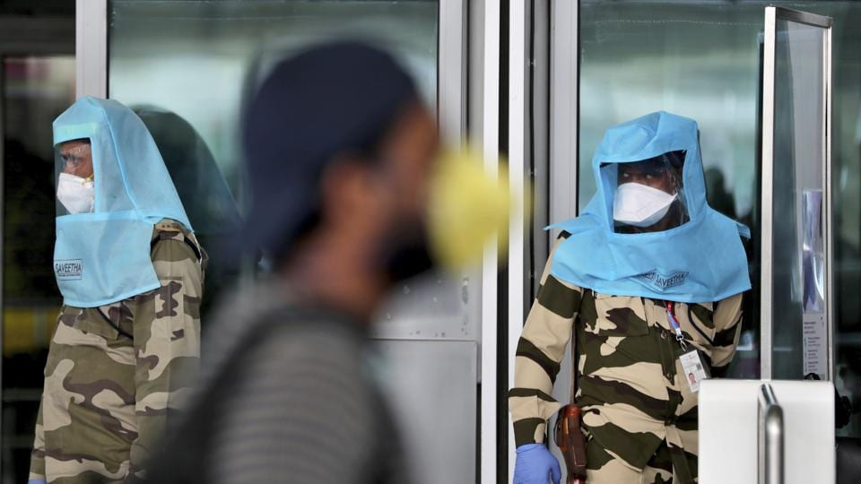 A passenger walks past Indian security personnel wearing protective gear at the departure terminal entrance of Kempegowda International Airport in Bengaluru, India.
