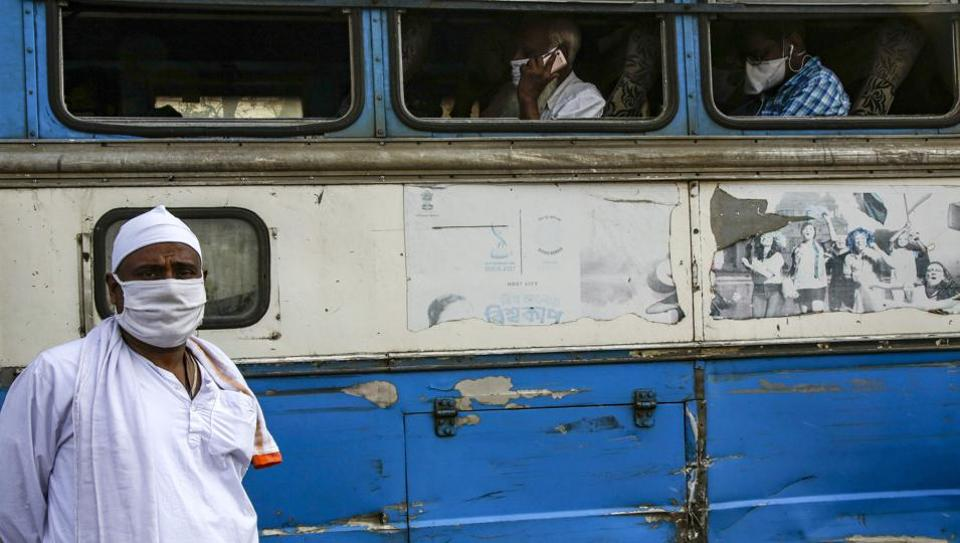 A masked passenger stands outside an interstate bus in Kolkata, in the eastern Indian state of West Bengal, Wednesday, June 3, 2020. More states opened up and crowds of commuters trickled onto the roads in many of India's cities on Monday as a three-phase plan to lift the nationwide coronavirus lockdown began despite an upward trend in new infections. (AP Photo/Bikas Das)