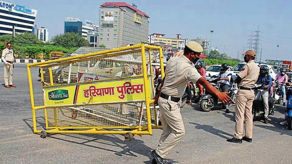 Gurugram police personnel remove barricades along the border with Delhi near Ambience Mall on Wednesday.