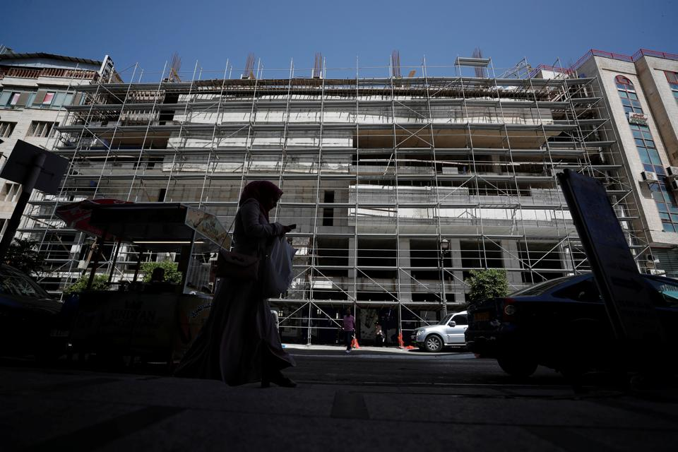A Palestinian woman walks past the construction site of an office building amid the coronavirus disease (COVID-19) crisis, in Ramallah in the Israeli-occupied West Bank June 2, 2020. REUTERS/Mohamad Torokman