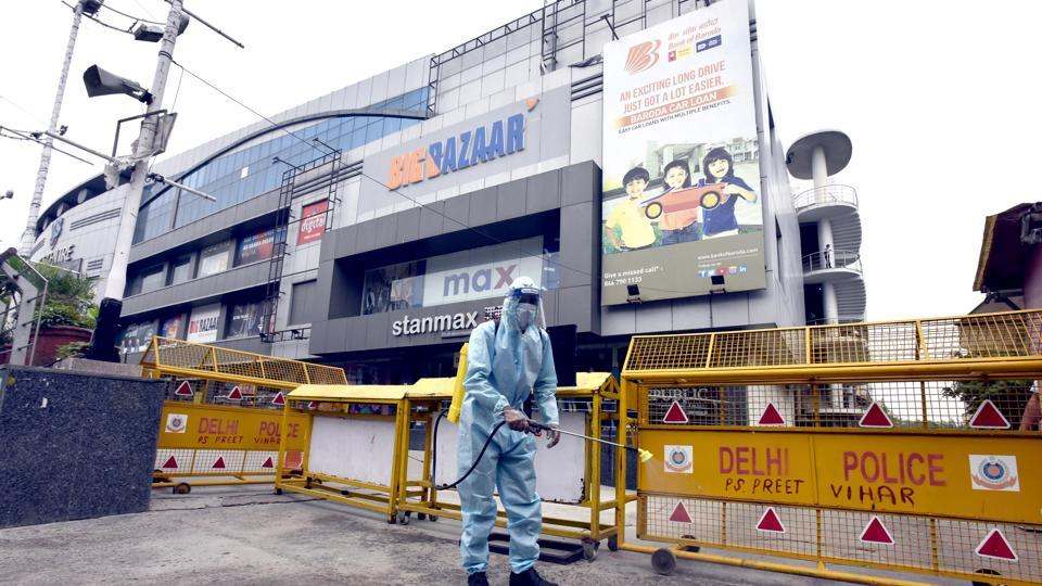 A worker wearing PPE sprays chemical disinfectant outside a mall in East Delhi's Laxmi Nagar on Thursday.