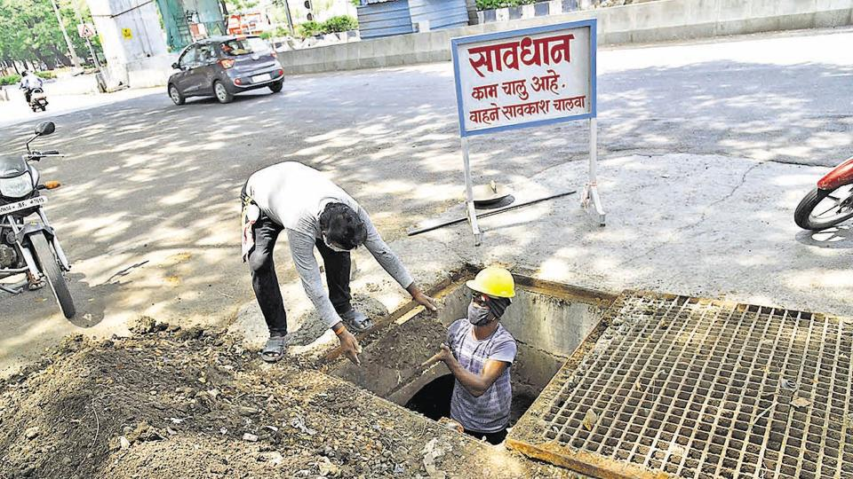 PCMC sanitation workers are seen cleaning a nullah (canal) on Friday, ahead of the monsoon.