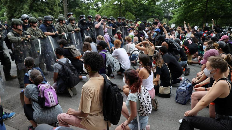 Demonstrators take a knee in front of law enforcement officers during a protest against the death in Minneapolis police custody of George Floyd, near the White House in Washington, US.