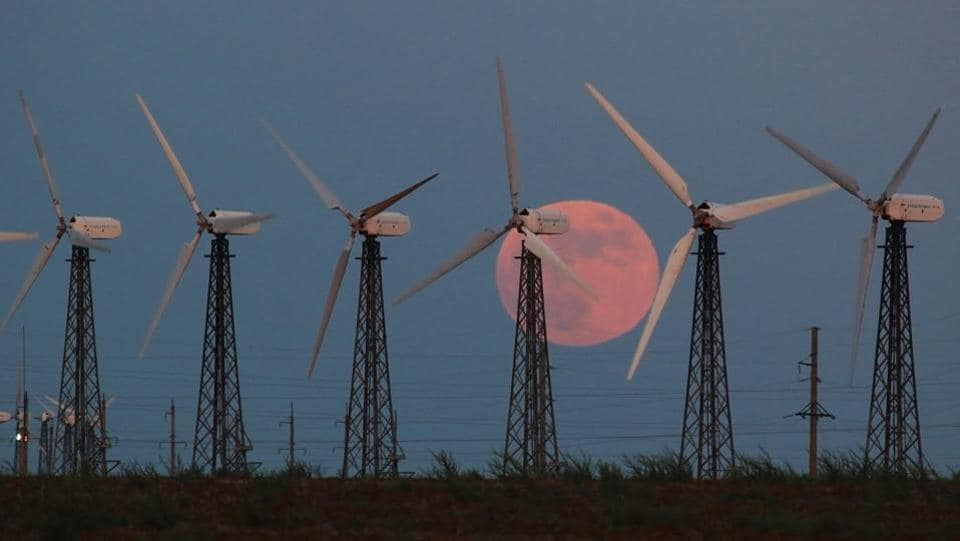 The moon rises behind power-generating windmill turbines near the settlement of Mirny, Crimea on June 5. A penumbral lunar eclipse occurs when the Sun, Earth, and the moon are imperfectly aligned. (Alexey Pavlishak / REUTERS)