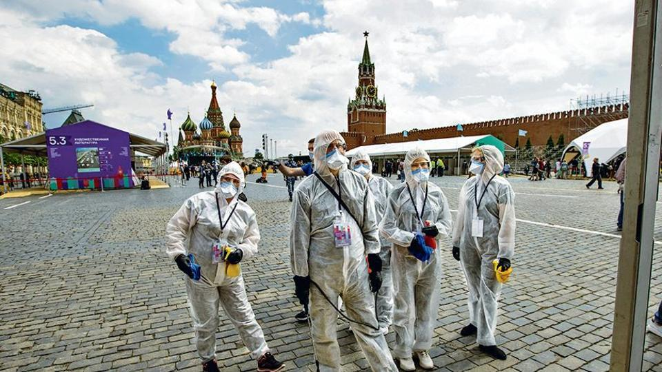 Volunteers in protective gear gather to clean an area of an outdoor book market set up at Red Square in Moscow on Saturday.