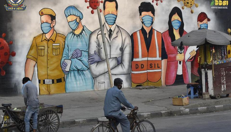 A cyclist rides past a mural - paying tribute to forntline coronavirus workers amid the lockdown, near Garhi Chowk, in New Delhi