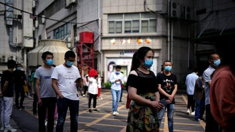 Residents wearing face masks line up for nucleic acid testings at a residential compound in Wuhan.