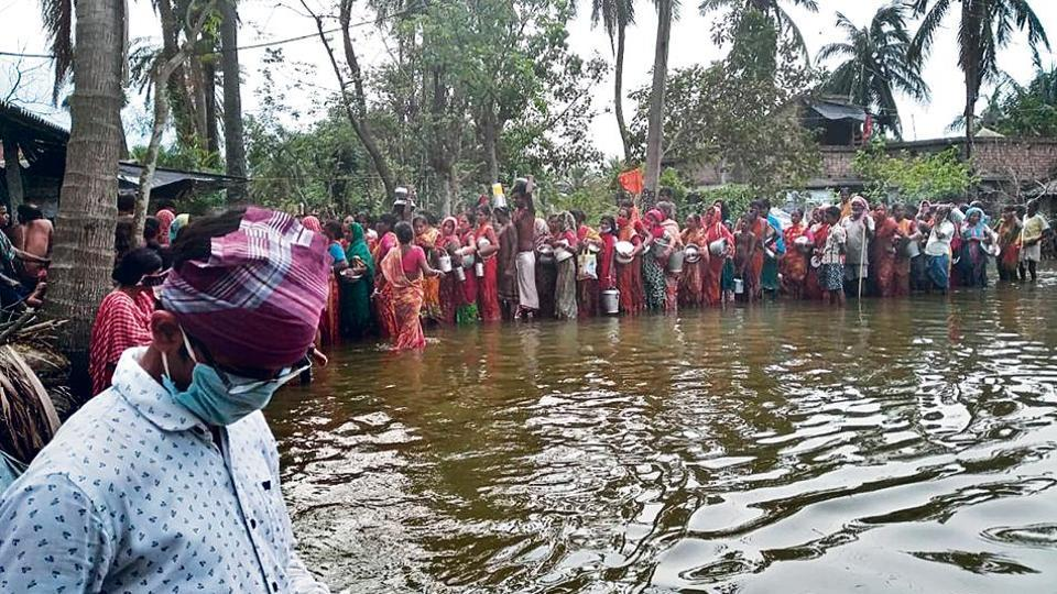 In Harinhula village, local residents line up for relief material as water levels rise due to the full-moon tide .