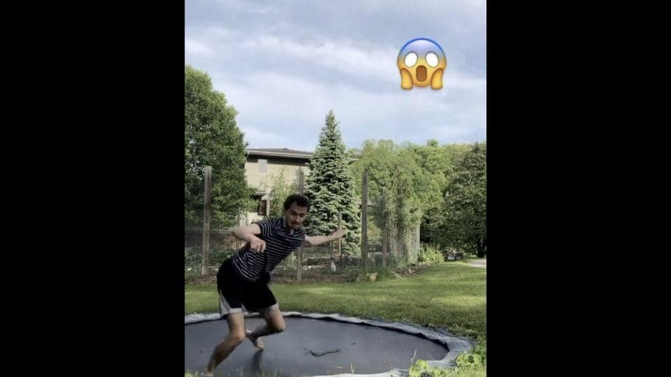 A snake joins a man on his trampoline, uninvited.