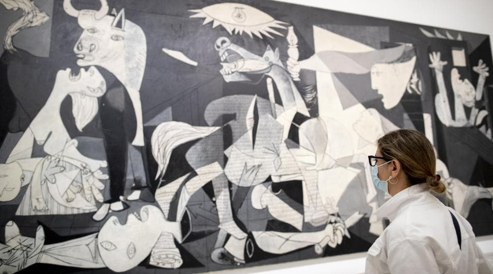 A visitor looks at Pablo Picasso's painting 'Guernica' as the Reina Sofia museum reopened to the public in Madrid, Spain, Saturday, June 6, 2020. Madrid's Museo del Prado opened its doors on Saturday for 1,800 visitors, after its closing during the coronavirus pandemic. The visitors were required to wear face masks and have their temperature taken before taking in what the museum called its