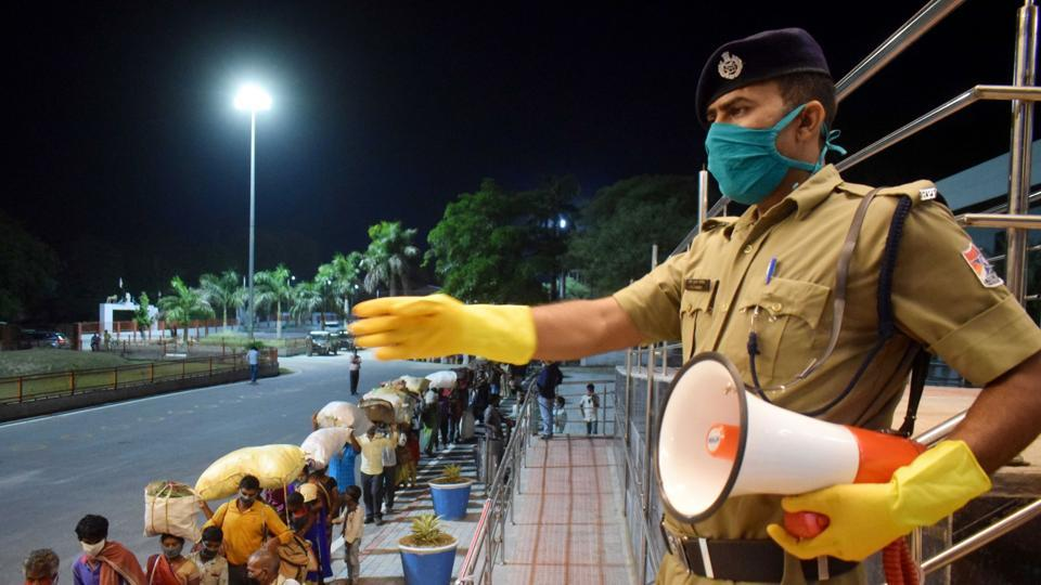 A police constable announces to maintain social distancing as migrants from Chhattisgarh arrive to board a special train to reach their native places at a railway station, during the ongoing COVID-19 lockdown, in Prayagraj.