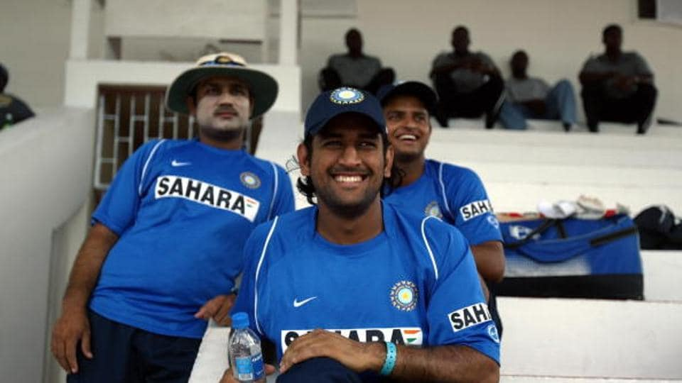 Indian cricketers Virender Sehwag(L), Mahender Singh Dhoni (C) and Suresh Raina(R) smile as they watch other teammates practice.