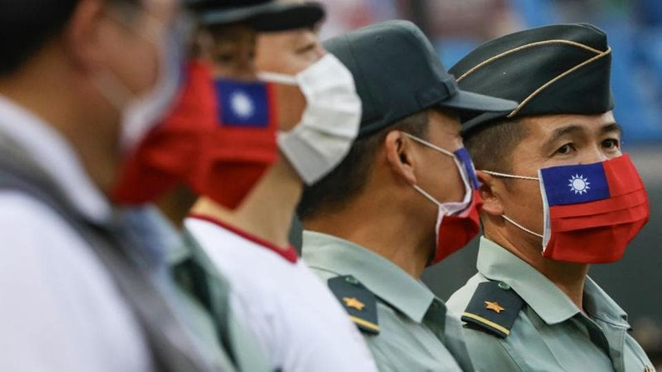 Army representative are seen at the opening of a baseball game with face masks decorated as a Taiwan flag to protect themselves from the coronavirus disease at a professional baseball league game in Taoyuan city, Taiwan.
