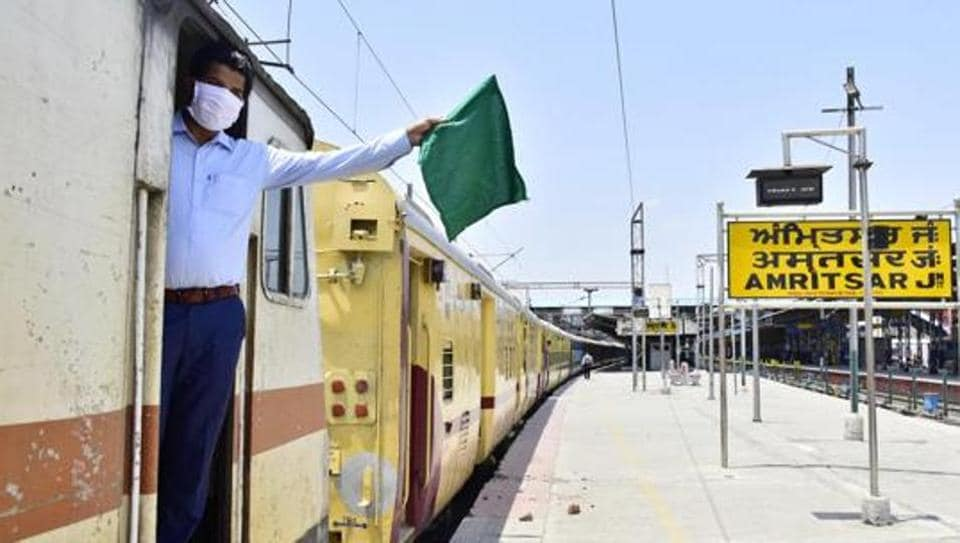 A railway guard waves the green flag aboard a Jaynagar Shaheed Express train at the Amritsar Junction as Indian Railways expand operations under lockdown on Monday.