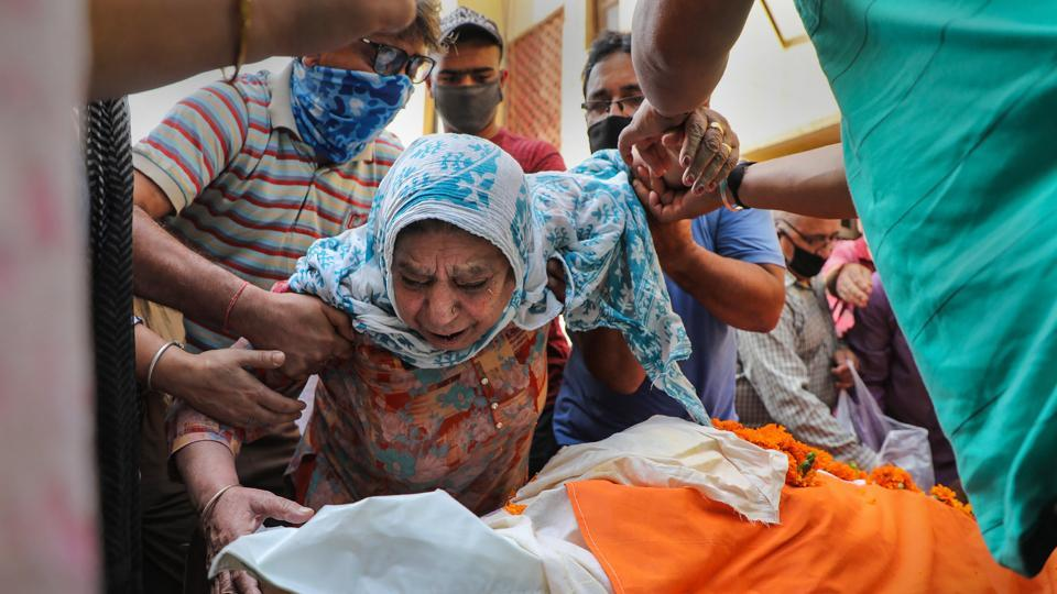 The mother of Kashmiri Pandit sarpanch Ajay Pandita mourns near his mortal remains, at their residence in Jammu on  June 9, 2020. Pandita was shot dead Monday evening by terrorists in Anantnag district of South Kashmir.