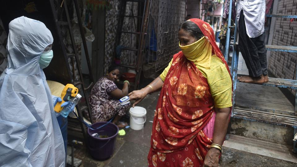 Health workers conduct Covid-19 test at Dharavi slum in Mumbai on Thursday.