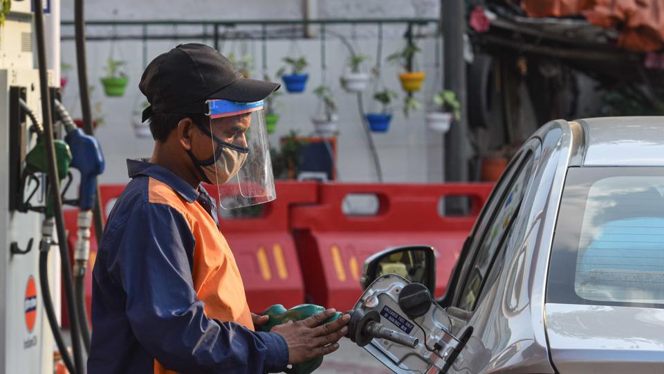 A petrol pump employee wearing a face shield while attending to a customer in Wazirpur, New Delhi.