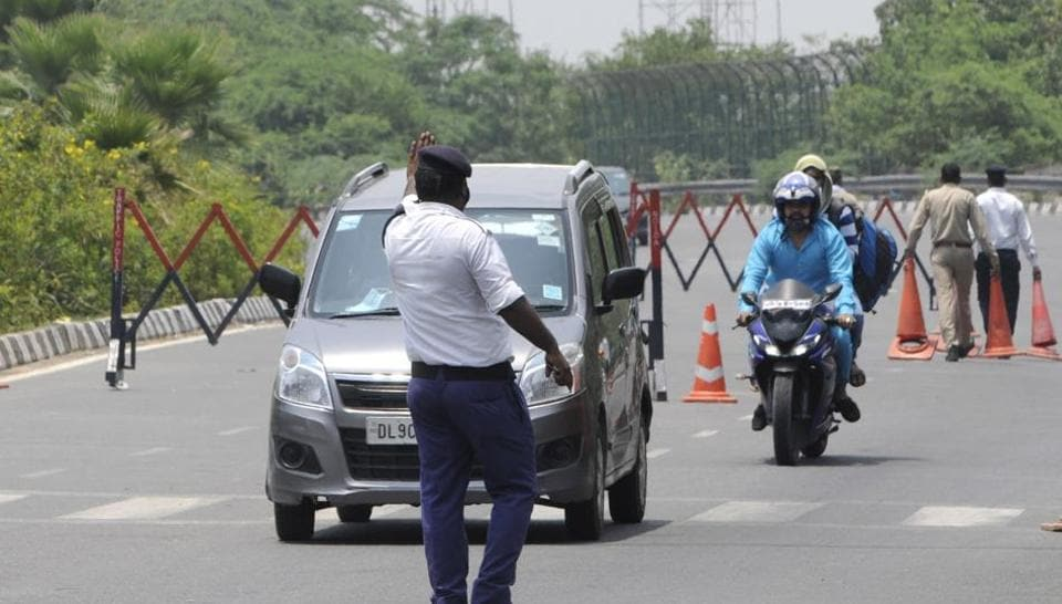 Uttar Pradesh traffic police personnel directing vehicles at Noida Gate along the Uttar Pradesh-Delhi border in Noida on Friday.