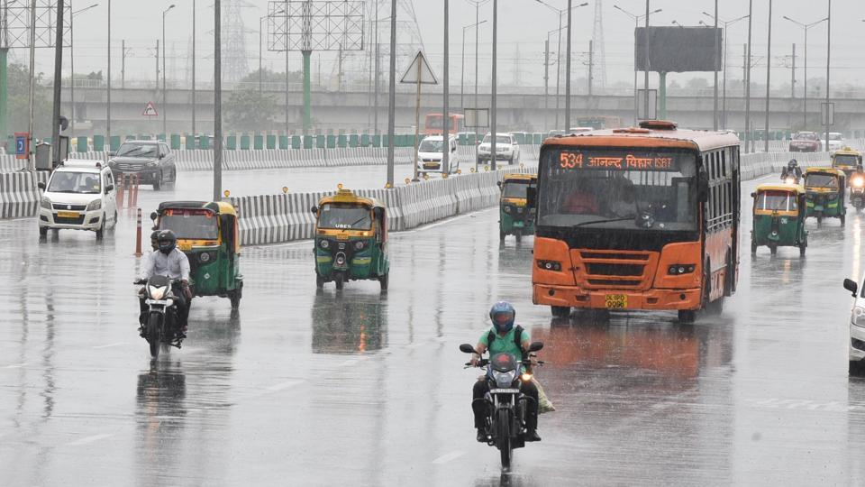 Commuters on the road while it rains at National Highway 24 near Akshardham Temple in East Delhi on Saturday.