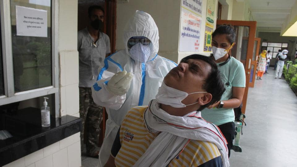 A doctor in PPE coveralls collects swab sample from people for coronavirus testing, during lockdown at Primary Health Centre (PHC) Wazirabad in Gurugram on Saturday.