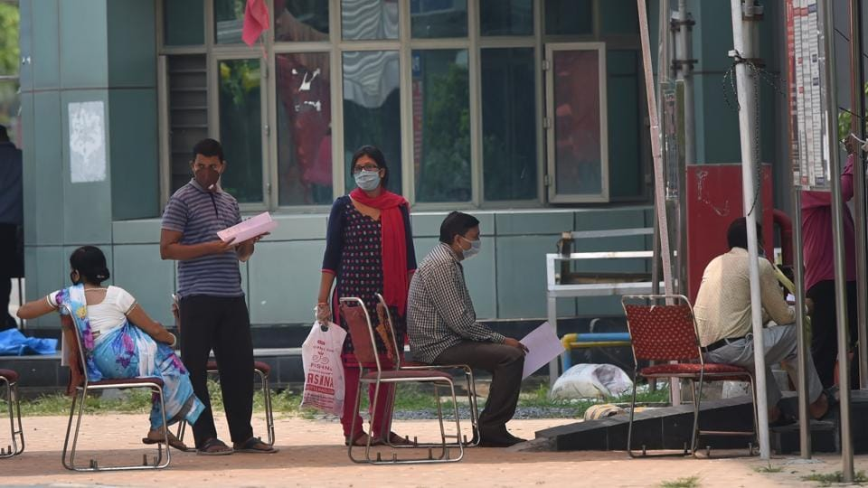 Suspected Covid-19 patients wait to be examined by medics at a government hospital in East Delhi on Saturday.