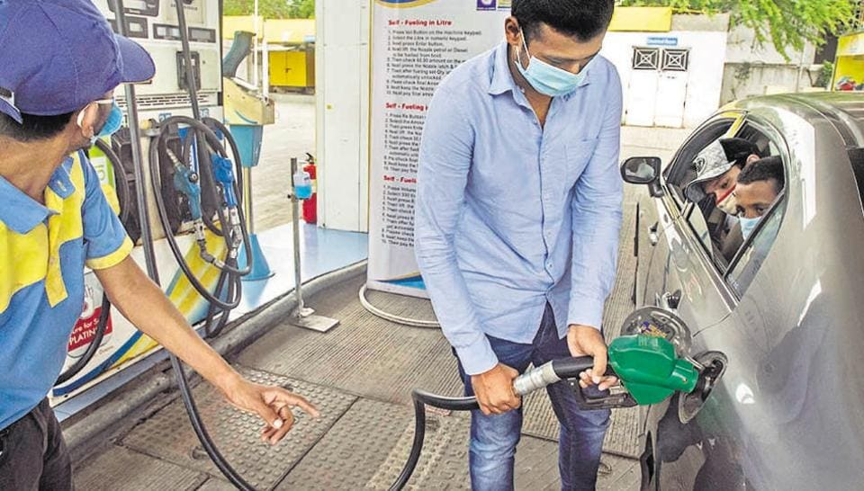 A customer fills fuel in his vehicle with the guidance of a staff member at a self service fuel station near RTO in Pune on Sunday.