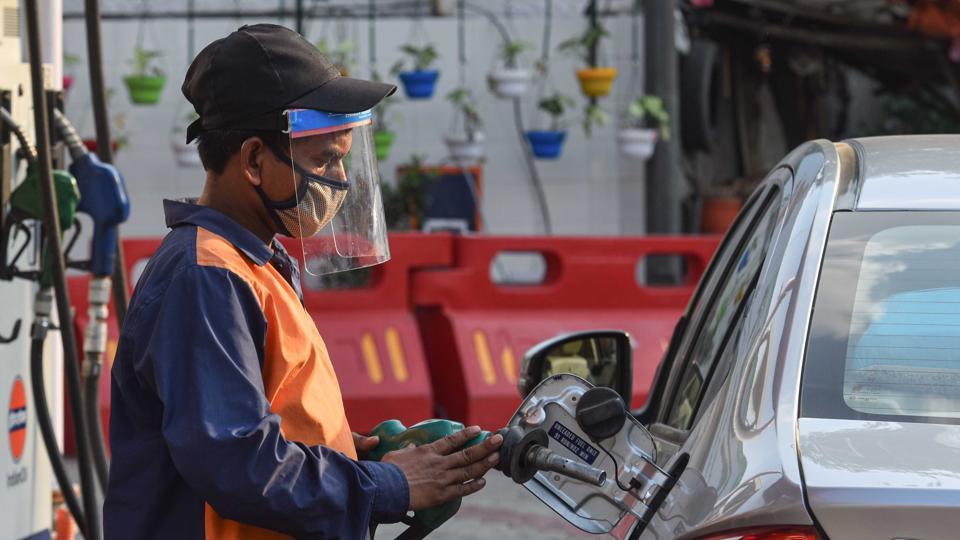 A petrol pump employee wearing a face shield while attending to a customer in Wazirpur, New Delhi