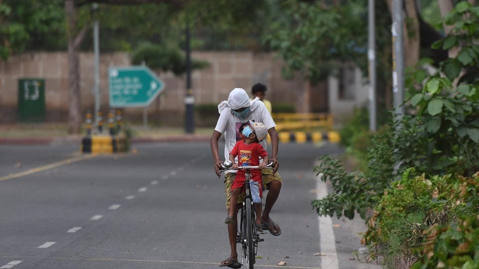A cyclist travelling with a child at Connaught Place in New Delhi.