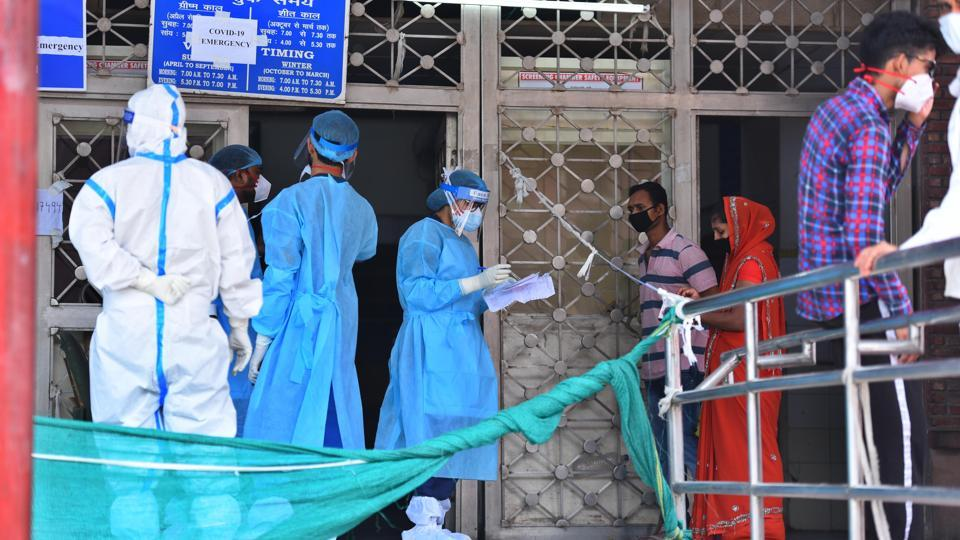 Medical workers speak with family members of people admitted with coronavirus infections, outside the Covid-19 ward at Lok Nayak Jai Prakash Narayan Hospital in New Delhi on Sunday.