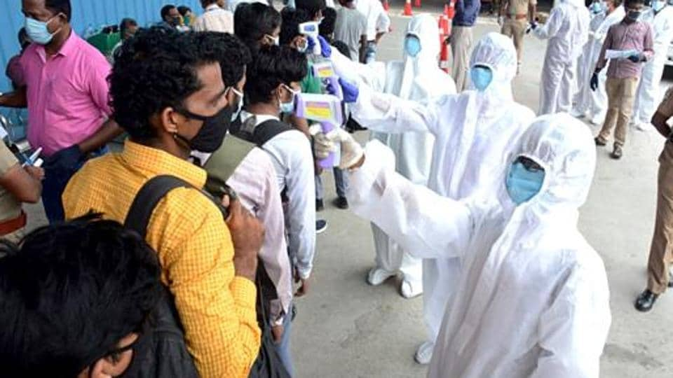 Medics check temperature of stranded migrant labourers queuing to board a special train to Madhya Pradesh from MGR Central railway station in Chennai, Tamil Nadu.