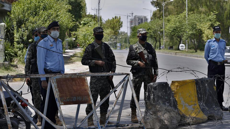 Pakistan paramilitary soldiers and a police officers stand guard at a checkpoint of a restricted area in Islamabad, Pakistan