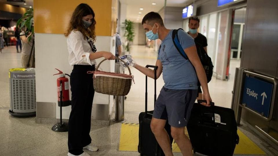 An Athens airport employee hands over free protective face masks and hand sanitiser to passengers of a flight from Paris as they arrive at the Eleftherios Venizelos International Airport, following the easing of measures against the spread of coronavirus disease (COVID-19), in Athens, Greece, June 15, 2020. REUTERS/Alkis Konstantinidis