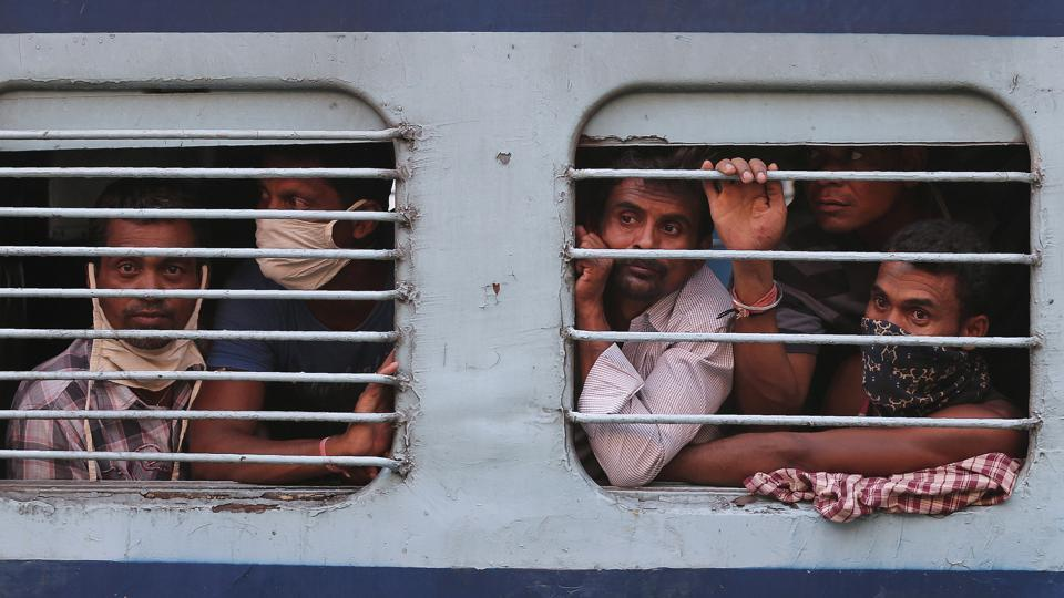 Migrant workers look out a train window before moving to their home states, at a railway station in Hyderabad, India.