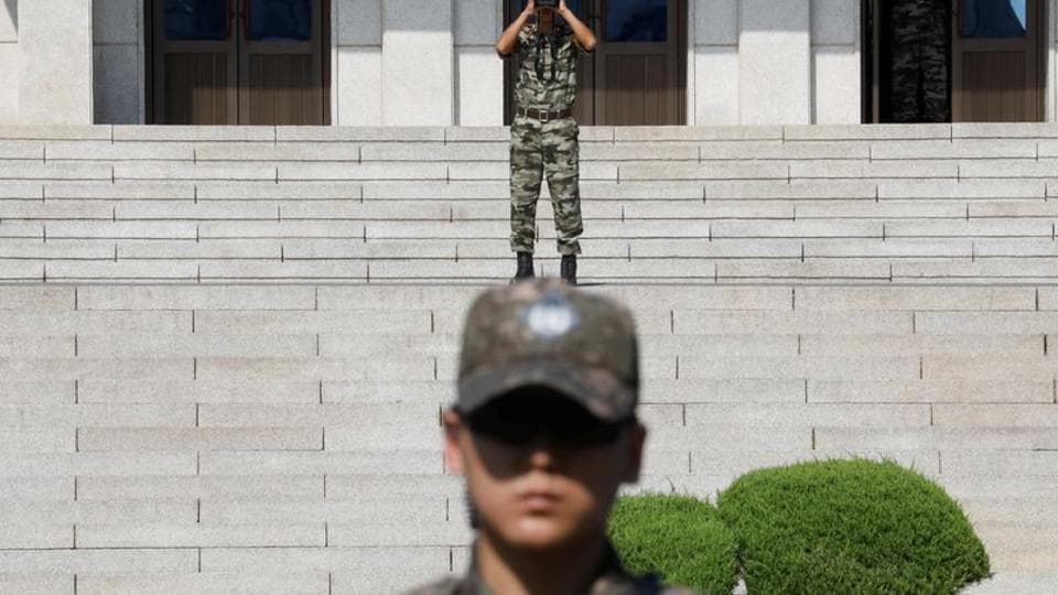 A North Korean soldier looks toward the south as a South Korean soldier stands guard in the truce village of Panmunjom inside the demilitarized zone (DMZ) separating the two Koreas, South Korea.
