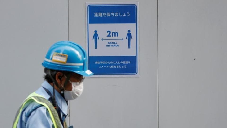 A worker wearing a protective face mask walks past a social distancing sign at the construction site of an office building, during the global outbreak of the coronavirus disease (COVID-19), in Tokyo, Japan June 2, 2020.