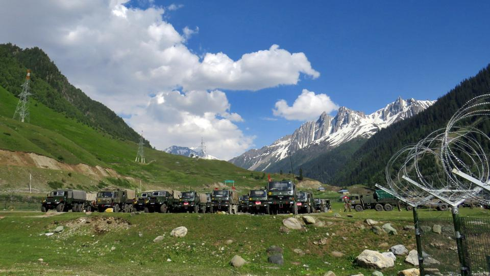 Indian army soldiers walk past their parked trucks at a makeshift transit camp before heading to Ladakh, near Baltal, southeast of Srinagar on June 16, 2020.