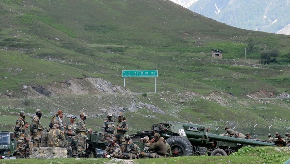 Indian army soldiers rest next to artillery guns at a makeshift transit camp before heading to Ladakh, near Baltal, southeast of Srinagar.